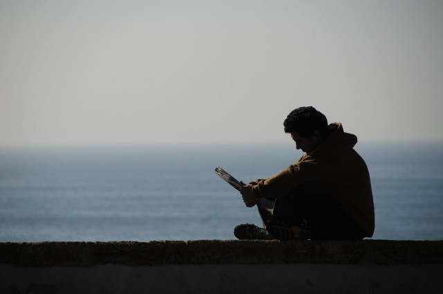 man reading by water